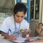 Person holding a bird. Golden Oriole. person writing.